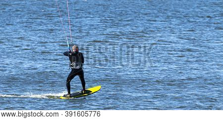 A Man Is Kite Surfing On A Yellow Surf Board In The Long Island Sound Wearing A Wet Suite.