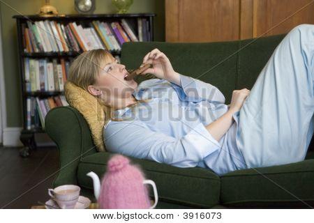 Woman On Sofa Eating Chocolate
