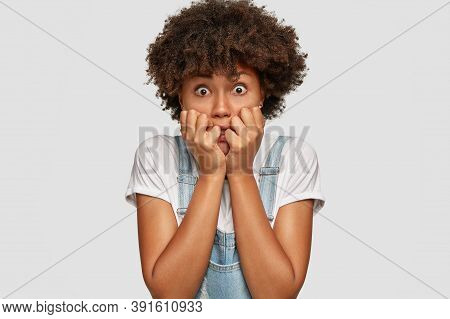 Nervous Anxious Woman Bites Finger Nails, Has Bugged Eyes, Feels Fear As Notices Phobia, Wears Denim