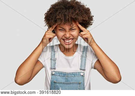 Desperate Displeased Dark Skinned Model Keeps Both Index Fingers On Temples, Has Headache, Suffers F