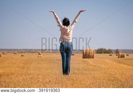 A Happy, Free, Independent, Dreamy Girl In The Field Raised Her Hands To The Sky. A Woman In A Jacke