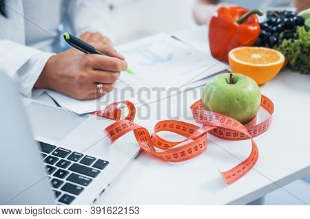 Female Nutritionist In White Coat Sitting Indoors In The Office At Workplace.