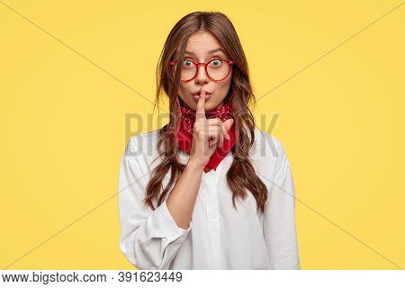 Horizontal Shot Of Secret Girl Makes Shush Gesture, Keeps Fore Finger Over Lips, Asks Not Spread Rum