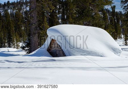 Heavy Snowfall Covering The Whole Hut. Fabulous Winter House Covered With Snow Up To The Roof In The