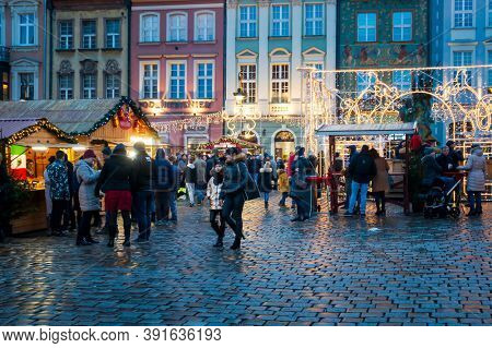 POZNAN, POLAND - December 15, 2019: Tourists on foot Graben Christmas Street Market, Poland