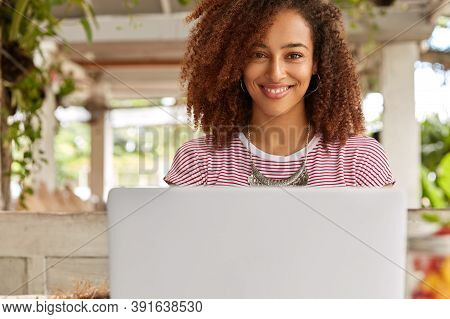 Horizontal Shot Of Pretty Female Freelancer Sits In Front Of Opened Laptop Computer, Being Satisfied