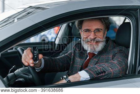 Modern Stylish Senior Man With Grey Hair And Mustache Holding Keys In Modern Car.