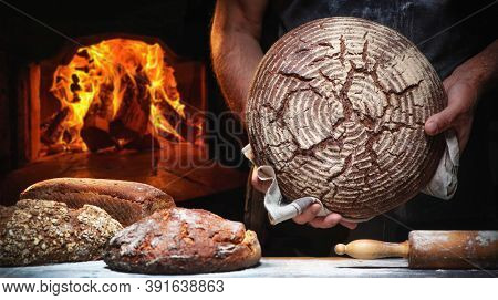 Baker's hands holding and presenting fresh baked loaf of bread in front of a burning oven