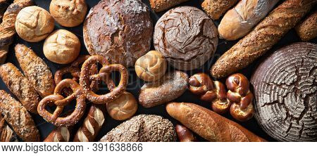 Delicious freshly baked bread assortment on dark rustic background. Top view
