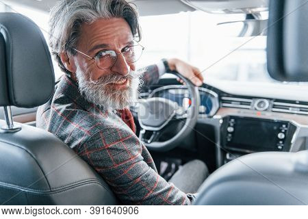 Positive Stylish Senior Man With Grey Hair And Mustache Looks Back In The Modern Car.
