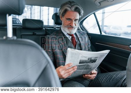 Modern Stylish Senior Man With Grey Hair And Mustache Reading Newspaper Inside Of The Car.