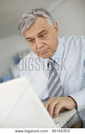 Senior businessman working on laptop with surprised look