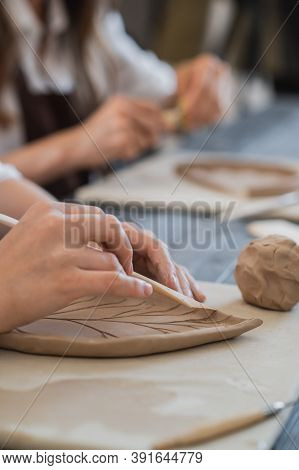 Female Hands Holding Stick And Making Ornament On Decorative Product. Clay Master Moulding Clay On A