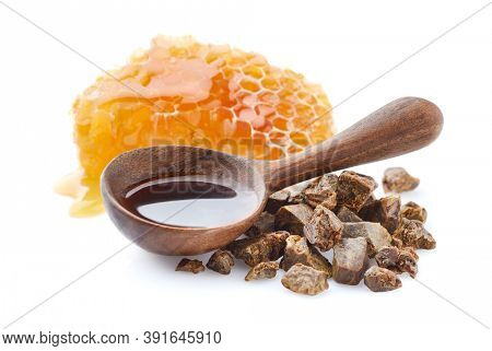 Propolis tincture in wooden spoon on white background. Natural antibiotic