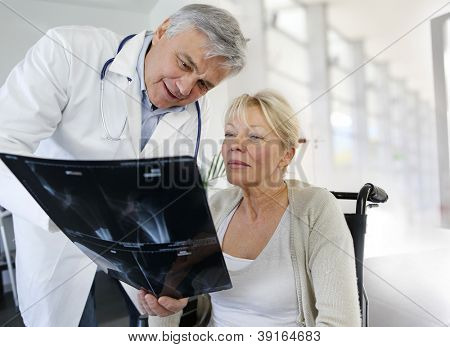 Surgeon showing X-ray result to woman in wheelchair