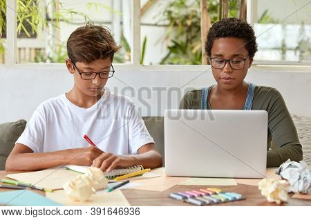 Photo Of Dark Skinned Woman Sits In Front Opened Laptop, Searches Information As Prepare For Seminar