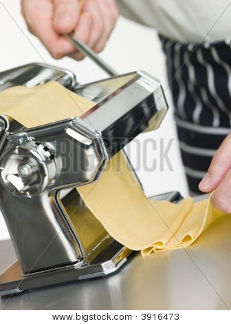 Fresh Egg Pasta Being Rolled In A Pasta Machine