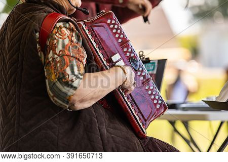Selective Focus Of Mature Person Wearing And Playing Accordion Musical Instrument With Reference Of