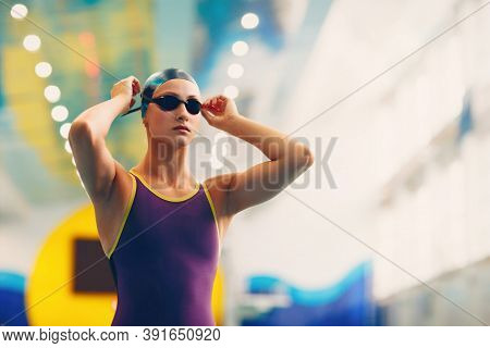 Young Woman Swimmer Professional Sportsman Wearing Cap And Glasses At The Swimming Pool Before The C