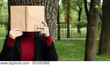 Portrait Of A Young Woman With An Open Untitled Book Held Close To Her Face. Brunette Covering Her F