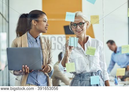 Wo Happy Female Coworkers Putting Colorful Sticky Notes On A Glass Wall And Smiling While Standing I