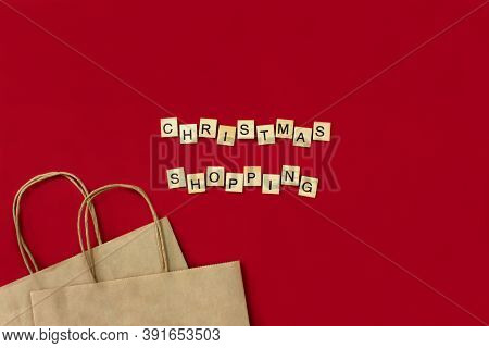 Christmas Shopping Phrase Made Of Wooden Blocks With Bags Flat Lay On Red Background Top View. Happy