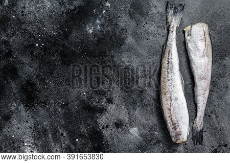 Raw Pollock Fish Ready To Cook. Black Background. Top View. Copy Space