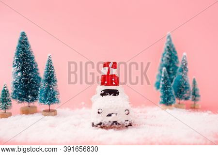 Miniature White Car Toy Delivering Gift Box And Christmas Tree On Pink Background. Christmas Greetin