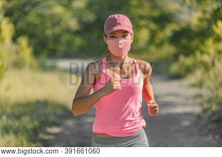 Mask wearing during exercise for COVID-19 protection. Asian girl running outside with face covering while exercising jogging in park wearing Pink mask.