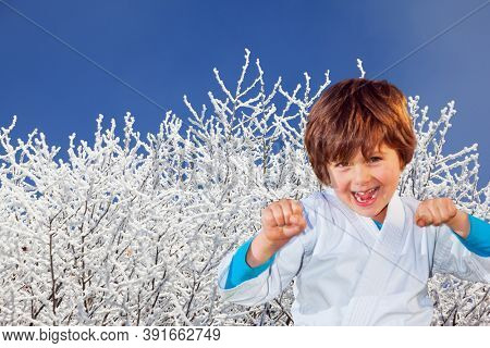 Handsome boy in judo uniform. Judo is a humane modern martial art. New Years is soon. Frosty snowy sunny day in the winter forest. Deep snow covered the ground.