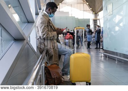 Afro-american Traveler Man In Trench Coat Wear Face Protective Mask, Sitting In Airport Terminal Or