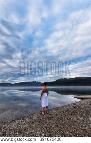 Man Standing By Water Ready To Go Swimming During A Cloudy Morning Sunrise. Taken At Fish Lake, Whit
