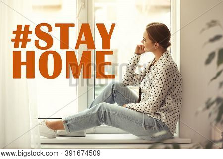 Hashtag Stayhome - Protective Measure During Coronavirus Pandemic. Young Woman Sitting On Window Sil