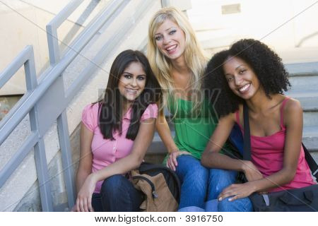 Three women sitting on staircase outdoors smiling (high key) poster
