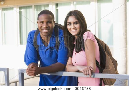 Two People Standing On Balcony Leaning On Railing