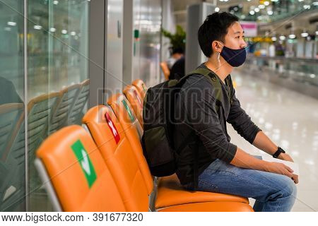 20s Young Adult Asian Male Tourist Backpacker Holding Flight Ticket Wearing A Face Mask With A Fligh