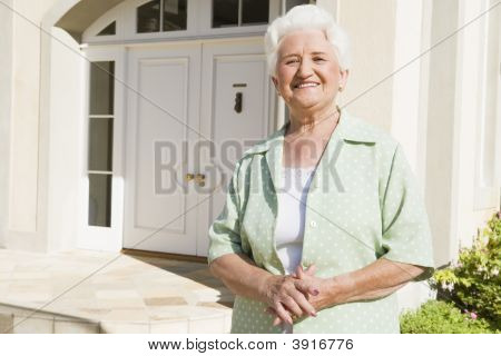 Senior Woman Standing Outside Her Home