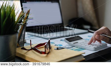 Accountant Working On Desk Using Calculator For Calculate Finance Report At Home