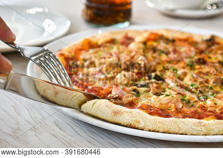 Hands With A Knife And Fork Cut A Slice Of Pizza. Fresh Pizza On A White Dish, Restaurant Interior.