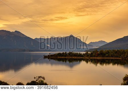Beautiful Lake Te Anau Scenery And Water Reflections Under A Vibrant  Orange Coloured Sky At Sunset