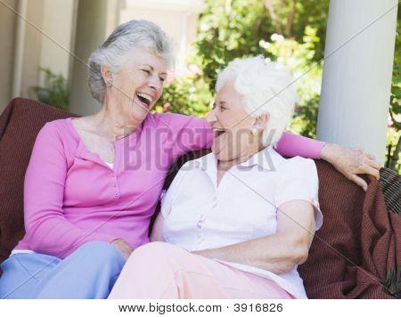 zwei senior DAMENLAUF im Freien sitzen auf einem Stuhl