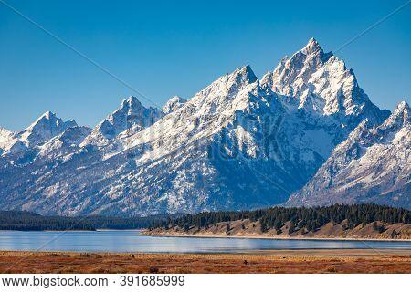 Snow Capped Mountain Range Of Grand Teton Over Willow Flats And Jackson Lake, Wyoming, Usa.