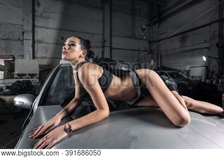 Portrait Woman In  Shorts And Top Posing Next To A  Car In The Garage, In Background Old Car. Creati
