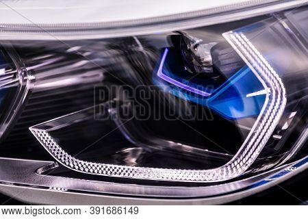 Glowing Headlight Of A Modern Car Close-up.  Car Xenon Lamp Headlight. Exterior Of A Exprnsive Car