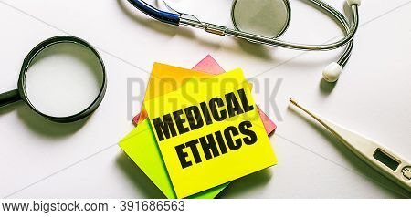 Medical Ethics Is Written On A Bright Sticker On A Light Background Near A Stethoscope, Magnifying G