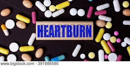 On A Dark Background, Multi-colored Pills And The Word Heartburn On A Wooden Block. Medical Concept