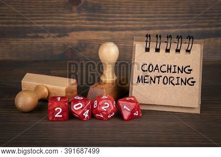 Coaching And Mentoring Concept. Red Dice And Wooden Stamps On The Table