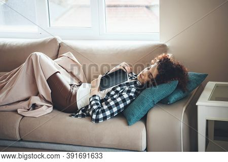 Curly Haired Student Is Sleeping In Bed Covered With A Coverlet After Reading A Book