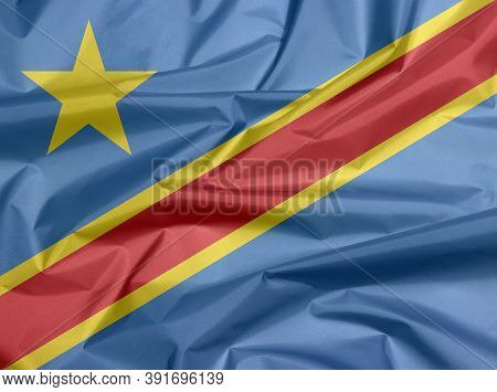 Fabric Flag Of Dr Congo. Crease Of Dr Congo Flag Background, Sky Blue Field With Diagonally Red And