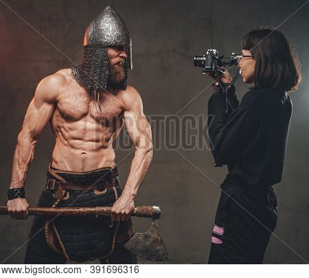 Shirtless And Muscular Guy With Axe And Helmet In Fashion Of Savage Viking Poses For Camera While Ph
